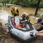 Conroe firefighters evacuate Jim Treadway via boat after Treadway was stranded when Pecan Bend Road was washed out  near the San Jacinto River on Friday, May 27, 2016, in Conroe, Texas. ( Brett Coomer/Houston Chronicle via AP) MANDATORY CREDIT