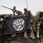 Nigerian soldiers hold up a Boko Haram flag that they had seized in the recently retaken town of Damasak, Nigeria, March 18, 2015. Chadian and Nigerien soldiers took the town from Boko Haram militants earlier this week. The Nigerian army said on Tuesday it had repelled Boko Haram from all but three local government districts in the northeast, claiming victory for its offensive against the Islamist insurgents less than two weeks before a presidential election. Picture taken March 18.    REUTERS/Emmanuel Braun - RTR4TZO2